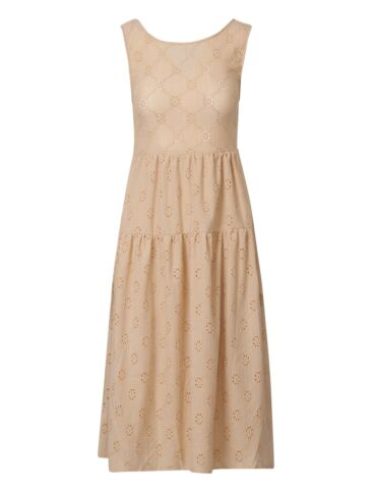 De beige, mouwloze jurk is gemaakt van embroderie en heeft een open rug met touwtjes.